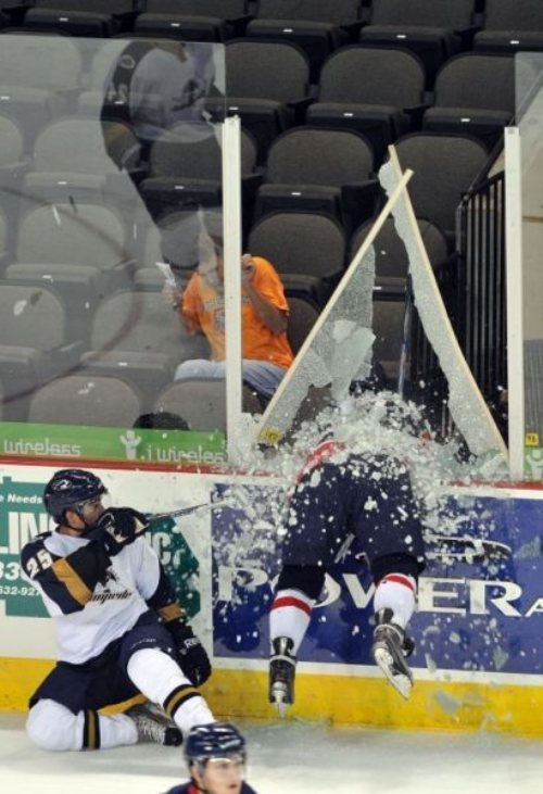 nicely_timed_sports_photos_hockey_player_crashed_through_thwe_fence