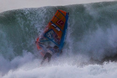 nicely_timed_sports_photos_wind_surfer_getting_hit_by_wave