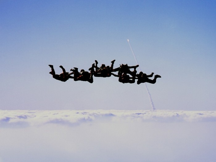 space_shuttle_discovery_being_launched_into_orbit_as_skydivers_descend-700x525